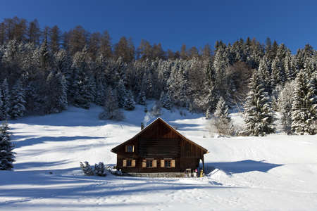 occupied: Rural sunny winter landscape with occupied chalet Editorial