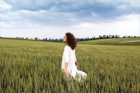 striding: Young white dressed adult is striding through field of cereal plant and let flow his thoughts