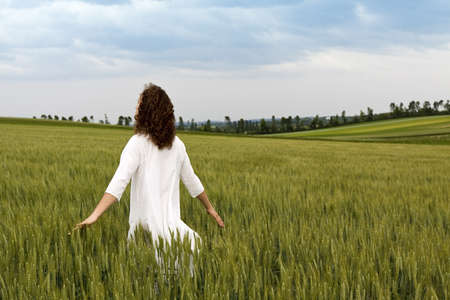 striding: Young adult is striding in a field of cereal plant and let flow his thoughts while his arms are outstretched and his view seems to search for something in the moody sky