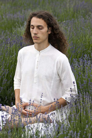 a young meditating yogi with closed eyes is sitting in a field of lavender photo