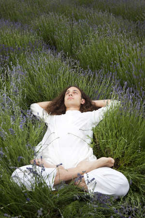 young man relaxing in a field of lavender photo