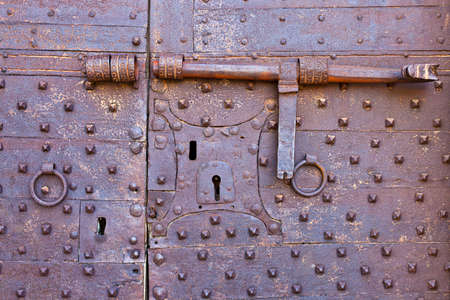 ancient prison: Old and rusty metal door with many keyholes and antique door latch