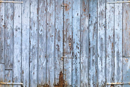 Old, grunge wood panels of wide light blue door photo