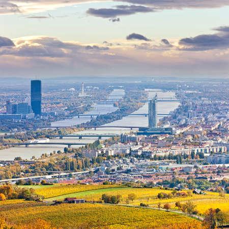 Cityscape van Wenen en de Donau in het najaar in de schemering op de juiste de zogenaamde Millennium Toren, aan de linkerkant van de Donau City met haar nieuwe DC Tower U kunt zelfs de luchthaven van Wenen en zijn witte Control Tower in de rug Stockfoto