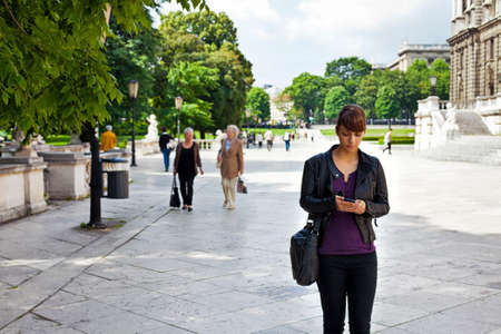 Smart and confident young woman striding through urban area beside a public park while she is using her mobile phone