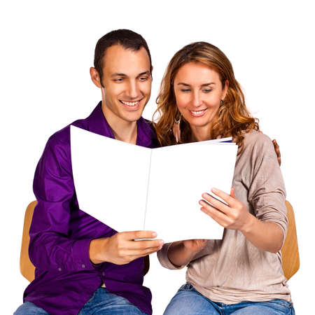 adult magazines: Young couple in love reading together a brochure with blank cover pages