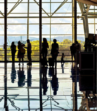 Silhouettes of unrecognizable traveling people at the airport in front of huge window with nature landscape in the background photo