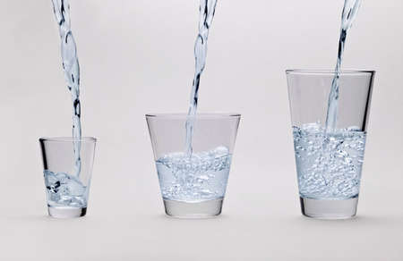 Pouring water into glasses on light gray background photo