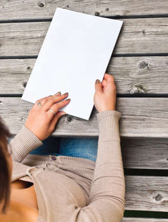 Joven sentado en la mesa de madera con un folleto con tapa blanca La cubierta blanca se puede utilizar para cualquier logo, señales de etiqueta o añadidos a los gráficos Foto de archivo - 26047808