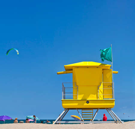 Yellow Life Guard Tower at the beach with people, kite surfer and blue sky. The Lifeguard have to protect the swimming people from the harmful kite surfer. photo