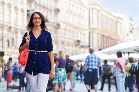 Cheerful urban girl standing out from the crowd at a city street. Stock Photo