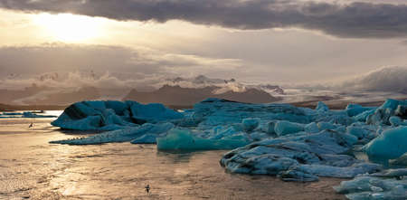 The sun sets over icebergs floating in the famous glacier lagoon at Jokulsarlon on the south coast of Iceland. photo