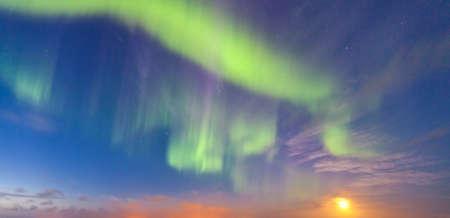 Real Nothern Lights aka Aurora Borealis with moon rising Stock Photo