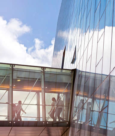 transition: Silhouettes of unrecognizable business people using a transition of a contemporary office building.