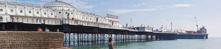 london to brighton: People enjoy a sunny day at the historic Brighton Pier. The beach between the West and Palace Piers has bars, restaurants, nightclubs, sports facilities and amusement arcades with daily visits exceed 150,000 at weekends in high summer.