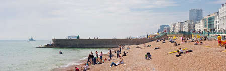 People enjoy a sunny day at the Brighton beach. The beach between the West and Palace Piers has bars, restaurants, sports facilities...