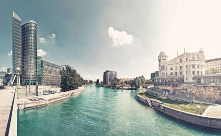 The Donaukanal (Danube Canal) of Vienna, Austria. At the left the new UNIQA-Tower and opposite the historic building Urania, a public educational institute and observatory. Picture Style achieved with digital cross processing technique.