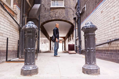 ramshackle: Confident young man in casual clothes standing in Urban surrounding in front of a passage in a ramshackle back alley. Stock Photo
