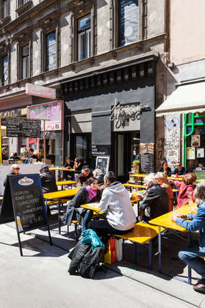 Some people enjoy a sunny day at the popular Viennese shopping street Neubaugasse. The street is small but always busy and full of little shops, theaters, culture and flea markets twice a year, which extends over the entire Neubaugasse.