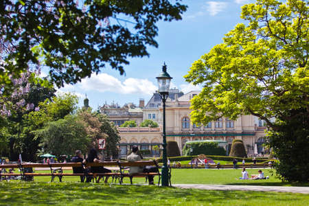 VIENNA, AUSTRIA - MAY 6, 2012: Some people enjoy a sunny recreational day at the Stadtpark Vienna with the Kursalon a historic and former music hall in the 18th century 新闻类图片