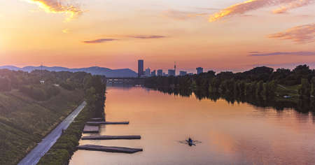 Dusk at the New Danube River with urban skyline of the Danube City and part of the Vienna Woods in the background