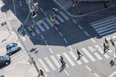 Some unrecognizable people crossing the street at a sunny day