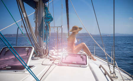 Beautiful woman on a sailboat enjoying the sun and the cool breeze of the ocean wind Stock Photo - 119551217