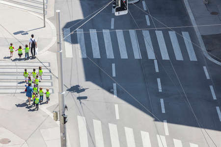 Some unrecognizable preschooler with their teachers crossing the street at a sunny day Stock Photo