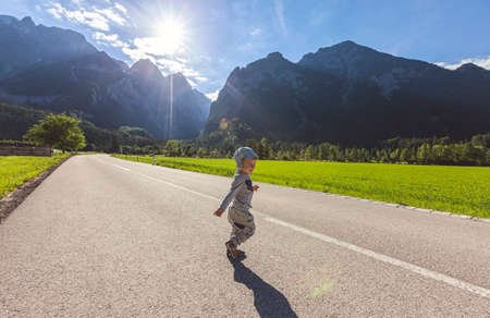 Little boy running on street surrounded by landscape and mountains Stock Photo