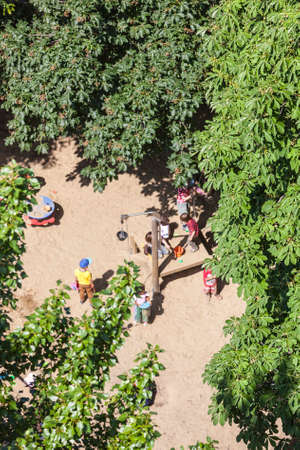 Aerial view of a sandy playground with some playing children surrounded by green trees.