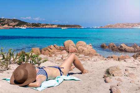 Beautiful woman on the beach enjoying the sun and the cool breeze of the ocean Stock Photo