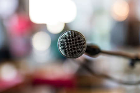 Close up of microphone in concert hall or meeting room with abstract blurred lights in background. Stock Photo
