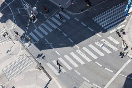 Some unrecognizable people crossing the street on a sunny day.