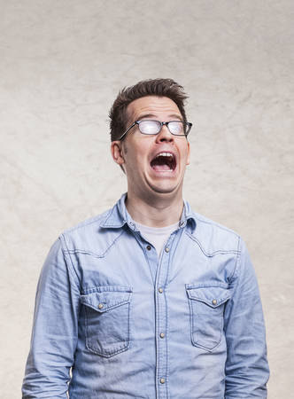 Portrait of a shocked, screaming, stunned or surprised young man - isolated on white light gray wall background.