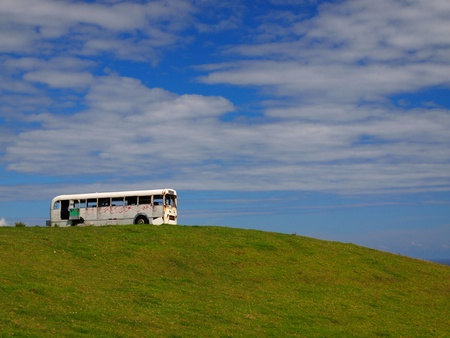 old bus taking the scenery in from the top of a hill photo