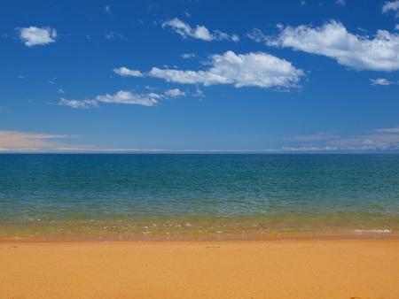 A tropical blue sea with golden sand beach and a perfect sky