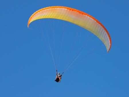 descends: parachitist duo descends in perfect blue sky Stock Photo