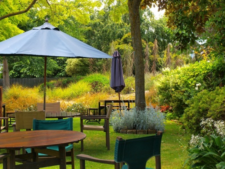 modern garden: dining table in sunny garden patio with sunshade