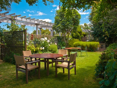 a wooden dining table set in lush garden setting photo