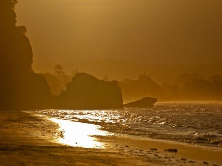 An orange glow sunset over a rocky coast Stock Photo - 10834420