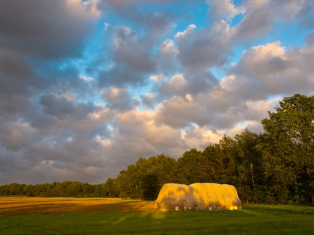 hay stack during sunset with dramatic cloudy sky Stock Photo - 10834479