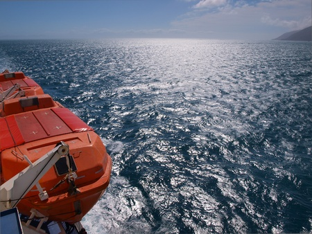a lifeboat on a the side of a ferry above a deep blue sea photo