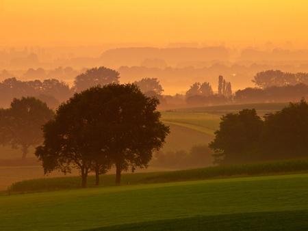 Orange sunrise over a misty agricultural landscape photo