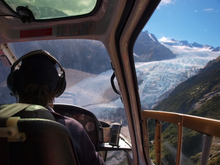 Helicopter pilot seen from behind above a glacier Stock Photo
