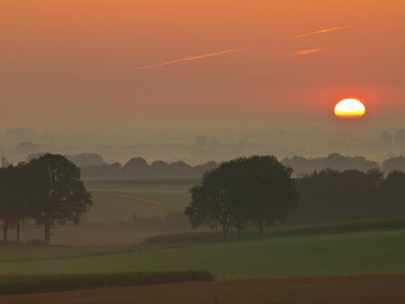 The sunis is rising over misty hilly farmland Stock Photo - 10834415
