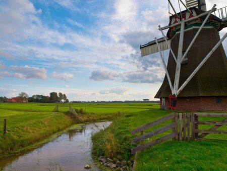 Typical dutch agricultural landscape with old vintage windmill photo