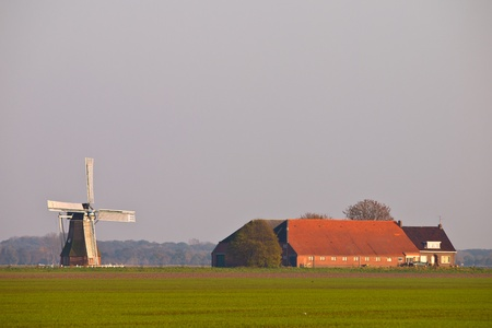 dutch agricultural landscape with farm and windmill photo