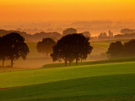 Orange sunrise over misty and hilly farmland Stock Photo - 11334407