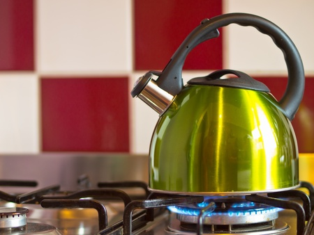 green kettle on a modern stove in front of a red with white wall