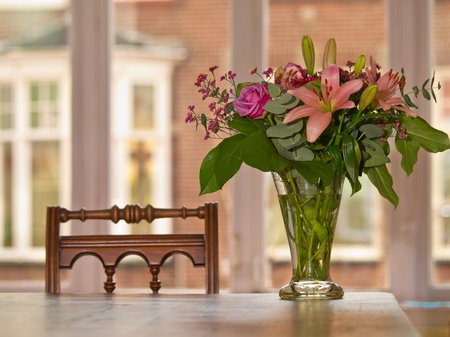 glass vase: pink bouqet on a table in a classic european apartment